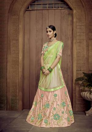 Look Pretty In This Designer Peach Colored Lehenga Choli Paired With Contrasting Light Green Colored Dupatta. It Is Satin Silk Based Beautified With Attractive Embroidery Paired With Net Fabricated Dupatta.  Buy Now.