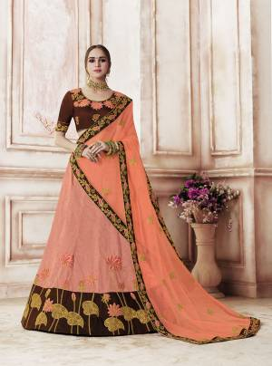 This Wedding Season Look The Most Amazing Of All Wearing This Designer Lehenga Choli In Brown Colored Blouse Paired With Contrasting Dark Peach Colored Lehenga And Dupatta. This Rich Silk Based Lehenga Choli Is paired With Net Fabricated Dupatta.