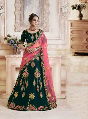 Catch All The Limelight Wearing This Heavy Designer Lehenga Choli In Dark Teal Green Colo Paired With Contrasting Pink Colored Dupatta. Its Blouse And Lehenga Are Silk Based Paired With Net Fabricated Dupatta. Its Rich Fabric And Color Pallete Will Earn You Lots Of Compliments From Onlookers.