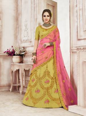 New Shade In Green Is Here With This Heavy Designer Lehenga Choli In Pear Green Color Paired With Contrasting Pink Colored Dupatta. This Lehenga Choli IS Fabricated On Art Silk Beautified With Heavy Embroidery Paired With Net Fabricated Dupatta.