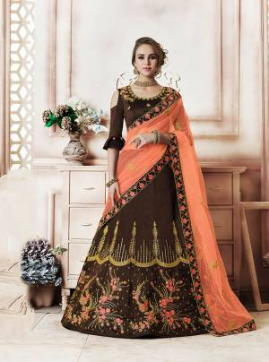 Another Rich Color Pallete Is Here With This Designer Lehenga Choli In Brown Color Paired With Contrasting Dark Peach Colored Dupatta. This Lehenga Choli Is Silk Based Paired With Net Fabricated Dupatta. Buy This Now.