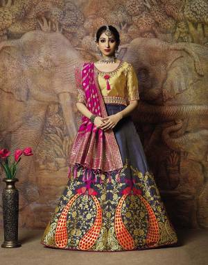 Adorn A Proper Traditional Look Wearing This Heavy Designer Lehenga Choli In Golden Colored Blouse Paired With Dark Grey Colored Lehenga And Rani Pink Colored Dupatta. This Lehenga And Blouse Are Fabricated On Jacquard Silk Paired With Brocade Fabricated Blouse.