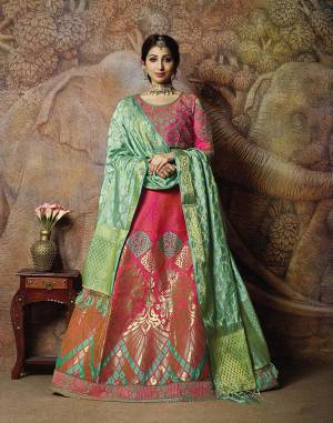 You Will Definitely Earn Lots Of Compliments In This Rich Silk Based Designer Lehenga Choli. Its Blouse Is In Dark Pink Color Paired With Dark Pink Colored Lehenga And Light Green Colored Dupatta. It Is Beautified With Bold Weave And Subtle Embroidery Over The Blouse. Buy This Silk Based Lehenga Choli Now.