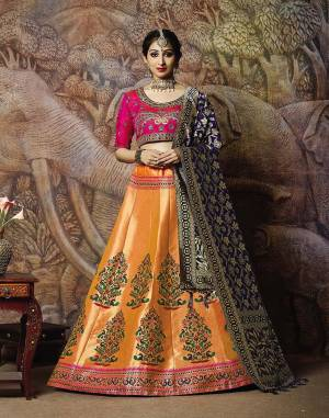 Catch All The Limelight In The Next Wedding You Attend With This Designer Lehenga Choli In Rani Pink Colored Blouse Paired With Contrasting Orange Colored Lehenga And Navy Blue Colored Dupatta. Its Lehenga Are Dupatta Are Fabricated On Jacquard Silk PAired With Art Silk Fabricated Blouse.