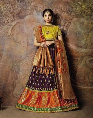Adorn A Proper Traditional Look Wearing This Heavy Designer Lehenga Choli In Yellow Colored Blouse Paired With Wine Colored Lehenga And Rust Orange Colored Dupatta. This Lehenga And Blouse Are Fabricated On Jacquard Silk Paired With Brocade Fabricated Blouse.