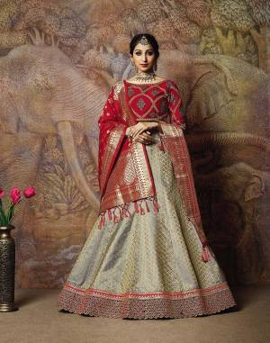 You Will Definitely Earn Lots Of Compliments In This Rich Silk Based Designer Lehenga Choli. Its Blouse Is In Red Color Paired With Grey Colored Lehenga And Red Colored Dupatta. It Is Beautified With Bold Weave And Subtle Embroidery Over The Blouse. Buy This Silk Based Lehenga Choli Now.