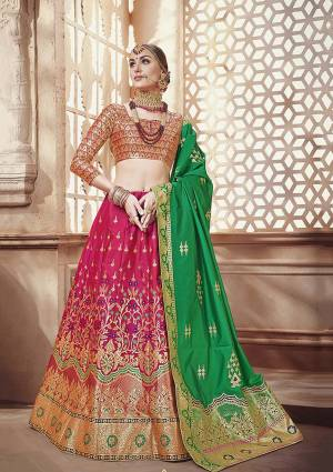 Celebrate This Festive Season with Beauty And Comfort Wearing this Designer Silk Based Lehenga Choli In Multi Colored Blouse Paired With Dark Pink Colored Lehenga And Green Colored Dupatta. It Is Beautified With Weave All Over.