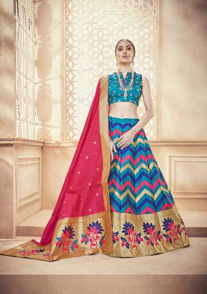 Here Is A Very Pretty Designer Lehenga Choli In Blue Color Paired With Contrasting Dark Pink Colored Dupatta. This Whole Lehenga Choli And Dupatta Are Fabricated On Banarasi Art Silk Beautified With Weave.