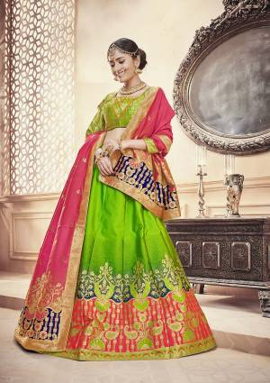Attract All In This Designer Silk Based Lehenga Choli In Parrot Green Color Paired With Contrasting Dark Pink Colored Dupatta. This Lehenga Choli And Dupatta Are Fabricated On Banarasi Art Silk Beautified With Weave. Buy Now.