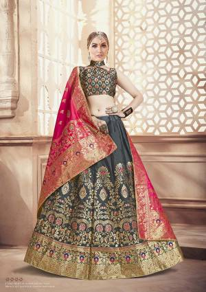 Flaunt Your Rich And Elegant Taste Wearing This Designer Lehenga Choli In Grey Color Paired With Contrasting Dark Pink Colored Dupatta. This Lehenga Choli And Dupatta Are Fabricated On Banarasi Art Silk Beautified With Weave.