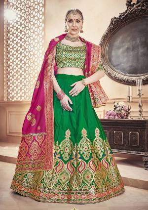 For A Proper Traditional Look, Grab This Designer Lehenga Choli In Green Color Paired With Contrasting Dark Pink Colored Dupatta. It Is Fabricated On Banarasi Art Silk Beautified With Attractive Weave.