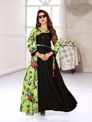 For Your Semi-Casuals, Grab This Readymade Gown In Black And Green Color Fabricated On Rayon. It Is Beautified With Bold Floral Prints And Available In All Regular Sizes.