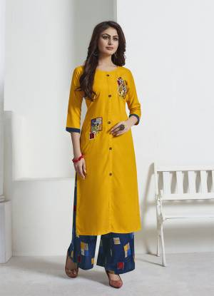Celebrate This Festive Season With Beauty And Comfort Wearing This Readymade Pair Or Kurti And Pant. Its Kurti Is In Yellow Color Paired With Contrasting Blue Colored Bottom. This Pretty Pair Is Rayon Based Beautified With Prints And Thread Work.