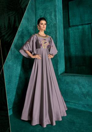 New And Unique Shade In Purple Is Here With This Designer Readymade Gown In Mauve Color Fabricated On Soft Art Silk. It Has Very Graceful Bell Sleeve Pattern And Beautified With Contrasting Embroidery.