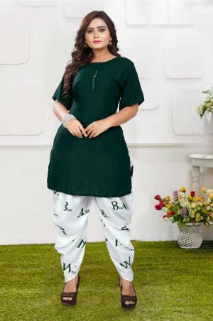 Grab This Pretty Pair Of Readymade Kurti And Dhoti In Pine Green And White Color. This Kurti Is Fabricated On Rayon Slub Paired With Crepe Fabricated Digital Printed Dhoti. It Is Available In All Regular Sizes And Ensures superb Comfort All Day Long. Buy Now.