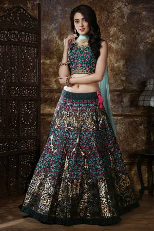 Get Ready For The Upcoming Wedding Season Wearing This Heavy Designer Lehenga Choli In Dark Green Color Paired With Contrasting Aqua Blue Colored Dupatta. This Lehenga Choli Is Silk Based Paired With Net Fabricated Dupatta. It Is Beautified With Multi Colored Prints And Resham Work With Foil Print.
