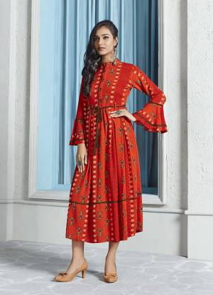 Shine Bright In This Readymade Designer Calf Length Kurti In Orange Color Fabricated On Rayon. Its Fabric Is Soft Towards Skin And It Is Beautified With Prints, It Is Easy To Carry All Day Long.