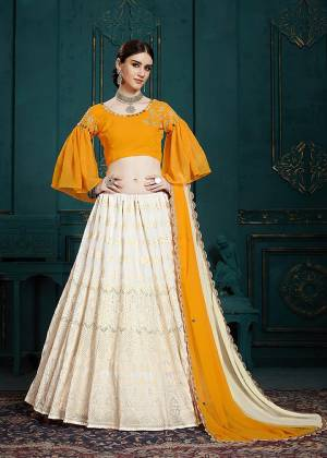 Celebrate This Festive And Wedding Season With Beauty And Comfort Wearing This Lovely Designer Piece In Musturd Yellow Colored Blouse Paired With Off-White Colored Lehenga And Dupatta. It Is Beautified With Embroidery And Attractive Mirror Work.