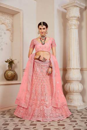 This Wedding Season Be The Most Sensational Diva Wearing This Heavy Designer Lehenga Choli In Pink Color. This Pretty Blouse, Lehenga And Dupatta Are Fabricated On Net Beautified With Tone To Tone Coding And Resham Embroidery With Stone Work. Buy This Designer Piece Now.
