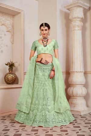 This Wedding Season Be The Most Sensational Diva Wearing This Heavy Designer Lehenga Choli In Light Green Color. This Pretty Blouse, Lehenga And Dupatta Are Fabricated On Net Beautified With Tone To Tone Coding And Resham Embroidery With Stone Work. Buy This Designer Piece Now.