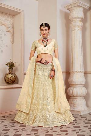 This Wedding Season Be The Most Sensational Diva Wearing This Heavy Designer Lehenga Choli In Pale Yellow Color. This Pretty Blouse, Lehenga And Dupatta Are Fabricated On Net Beautified With Tone To Tone Coding And Resham Embroidery With Stone Work. Buy This Designer Piece Now.
