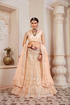 This Wedding Season Be The Most Sensational Diva Wearing This Heavy Designer Lehenga Choli In Light Peach Color. This Pretty Blouse, Lehenga And Dupatta Are Fabricated On Net Beautified With Tone To Tone Coding And Resham Embroidery With Stone Work. Buy This Designer Piece Now.