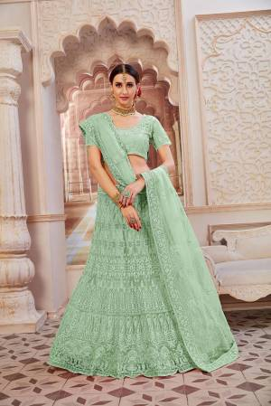 This Wedding Season Be The Most Sensational Diva Wearing This Heavy Designer Lehenga Choli In Mint Green Color. This Pretty Blouse, Lehenga And Dupatta Are Fabricated On Net Beautified With Tone To Tone Coding And Resham Embroidery With Stone Work. Buy This Designer Piece Now.