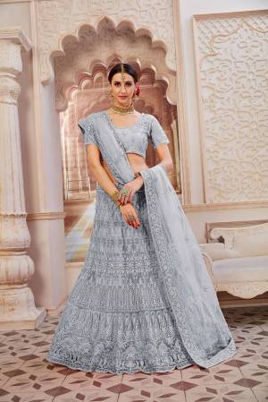 This Wedding Season Be The Most Sensational Diva Wearing This Heavy Designer Lehenga Choli In Grey Color. This Pretty Blouse, Lehenga And Dupatta Are Fabricated On Net Beautified With Tone To Tone Coding And Resham Embroidery With Stone Work. Buy This Designer Piece Now.