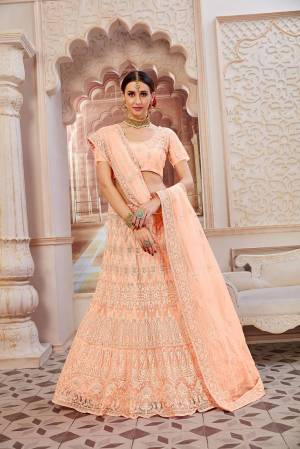 This Wedding Season Be The Most Sensational Diva Wearing This Heavy Designer Lehenga Choli In Peach Color. This Pretty Blouse, Lehenga And Dupatta Are Fabricated On Net Beautified With Tone To Tone Coding And Resham Embroidery With Stone Work. Buy This Designer Piece Now.