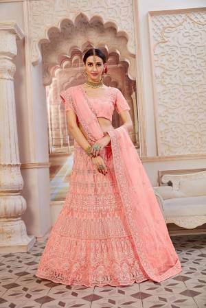 This Wedding Season Be The Most Sensational Diva Wearing This Heavy Designer Lehenga Choli In Light Pink Color. This Pretty Blouse, Lehenga And Dupatta Are Fabricated On Net Beautified With Tone To Tone Coding And Resham Embroidery With Stone Work. Buy This Designer Piece Now.
