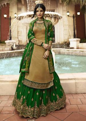 Celebrate This Festive And Wedding Season With This designer Indo-Western Lehenga Suit In Dark Beige Colored Top Paired With Contrasting Green Colored Lehenga And Dupatta. Its Top Is Satin Georgette Based Paired With Net Fabricated Lehenga And Dupatta.