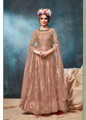 Get Ready For The Upcoming Wedding And Festive Season With This Heavy Designer Floor Length Suit In Dusty Peach Color. Its Heavy Embroidered op Is Fabricated On Net Paired With Santoon Bottom And Net Fabricated Dupatta. Buy Now.