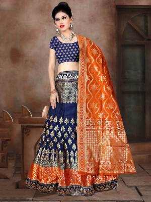 Shine Bright In This Very Beautiful Designer Lehenga Choli In Navy Blue Color Paired With Contrasting Orange Colored Dupatta. This Lehenga Choli Is Fabricated On Banarasi Jacquard Silk Beautified With Weave All Over.