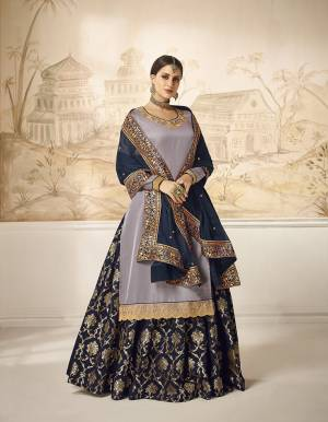 Choose Your Indo-Western Style As Per Occasion And You Can Get Its Bottom Stitched As Skirt Or Plazzo. Its Pretty Top Is In Mauve Grey Color Paired With Contrasting Navy Blue Colored Bottom And Dupatta. Its Top Is Fabricated On Satin Silk Paired With Jacquard Silk Bottom And Georgette Silk Fabricated Dupatta. Buy This Lovely Designer Piece Now.