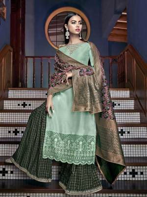 Pretty Shades In Green are Here With This Designer Sharara Suit In Sea Green Colored Top Paired With Dark Green Colored Bottom And Multi Colored Dupatta. Its Top Is Fabricated On Tussar art Silk Paired With Jacqurd Silk Bottom And Dupatta. It Is Beautified With Attractive Embroidery and Weaved Dupatta.