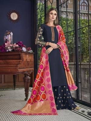 Enhance Your Personality Wearing This Designer Sharara Suit In Navy Blue Color Paired With Contrasting Dark Pink And Orange Colored Dupatta. Its Top Is Fabricated On Soft Art Silk Paired With Georgette Bottom And Jacquard Silk Fabricated Dupatta. It Is Light Weight And Easy To Carry All Day Long.