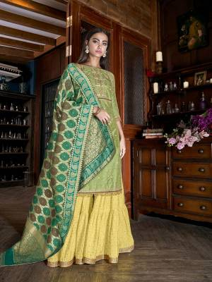 Celebrate This Festive Season With Pretty Colors Wearing This Designer Sharara Suit In Light Green Colored Top Paired With Contrasting Yellow Colored Bottom and Green Colored Dupatta. Its Top Is Fabricated On Art Silk Slub Paired With Muslin Bottom And Jacquard Silk Fabricated Dupatta.