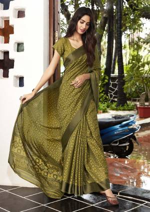 Grab This Very Beautiful Saree In Olive Green Color Paired With Olive Green Colored Blouse. This Saree And Blouse Are Fabricated On Kota Brasso Beautified With Prints All Over.