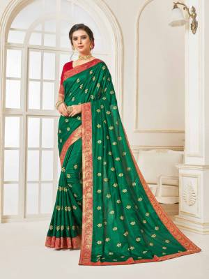 For A Proper Traditional Look, Grab This Designer Silk Based Saree In Dark Green Color Paired With Contrasting Red Colored Blouse. Its Rich Fabric And Color Will Earn You Lots Of Compliments From Onlookers.
