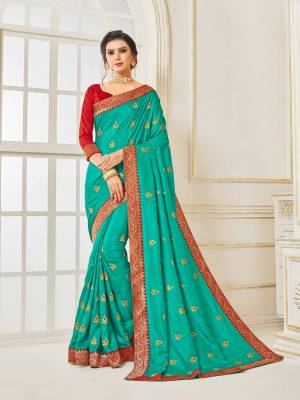 Grab This Very Beautiful Designer Saree In Turquoise Blue Color Paired With Contrasting Red Colored Blouse. This Saree And Blouse Are Silk Based Beautified With Embroidered Butti and Lace Border. Buy This Pretty Saree Now.