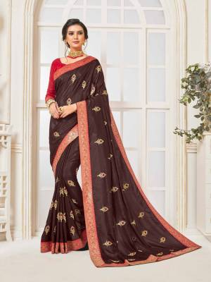 Enhance Your Personality Wearing This Designer Silk Based Saree In Brown Color Paired With Contrasting Red Colored Blouse. Its Rich Fabric Is Light Weight And Durable And Gives A Royal Look To Your Personality.