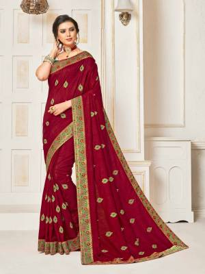 Shine Bright Wearing This Designer Silk Based Saree In Maroon Color Paired With Contrasting Green Colored Blouse. It Is Beautified With Embroidered Small Butti With Jacqurd Lace Border All Over, Buy Now.