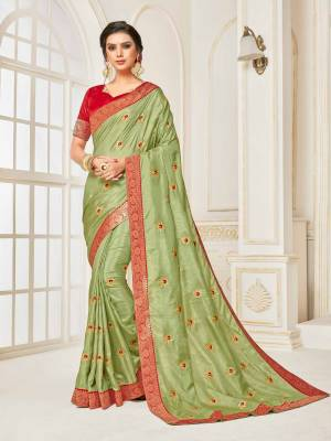 For A Proper Traditional Look, Grab This Designer Silk Based Saree In Light Green Color Paired With Contrasting Red Colored Blouse. Its Rich Fabric And Color Will Earn You Lots Of Compliments From Onlookers.