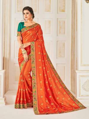 Celebrate This Festive Season Wearing This Designer Silk Based Saree In Orange Color Paired With Contrasting Teal Blue Colored Blouse. This Saree Is Beautified With Small Embroidered Buttis And Jacquard Lace Border.