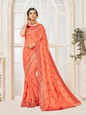 Grab This Very Beautiful Designer Saree In Dark Peach Color Paired With Contrasting Red Colored Blouse. This Saree And Blouse Are Silk Based Beautified With Embroidered Butti and Lace Border. Buy This Pretty Saree Now.