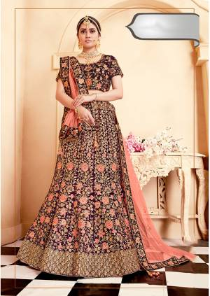 Get Ready For Your D-Day With This Heavy Designer Bridal Lehenga Choli In Wine Color Paired With Contrasting Dark Peach Colored Dupatta. Its Heavy Embroidered Blouse And Lehenga Are Fabricated On Velvet Paired With Net Fabricated Dupatta.