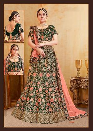 Get Ready For Your D-Day With This Heavy Designer Bridal Lehenga Choli In Dark Green Color Paired With Contrasting Dark Peach Colored Dupatta. Its Heavy Embroidered Blouse And Lehenga Are Fabricated On Velvet Paired With Net Fabricated Dupatta.