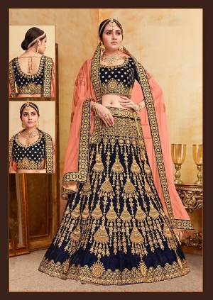 Get Ready For Your D-Day With This Heavy Designer Bridal Lehenga Choli In Navy Blue Color Paired With Contrasting Dark Peach Colored Dupatta. Its Heavy Embroidered Blouse And Lehenga Are Fabricated On Velvet Paired With Net Fabricated Dupatta.