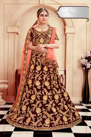 Get Ready For Your D-Day With This Heavy Designer Bridal Lehenga Choli In Maroon Color Paired With Contrasting Dark Peach Colored Dupatta. Its Heavy Embroidered Blouse And Lehenga Are Fabricated On Velvet Paired With Net Fabricated Dupatta.