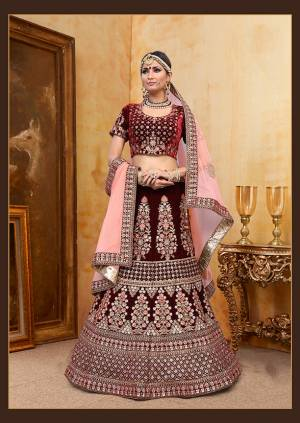 Get Ready For Your D-Day With This Heavy Designer Bridal Lehenga Choli In Maroon Color Paired With Contrasting Baby Pink Colored Dupatta. Its Heavy Embroidered Blouse And Lehenga Are Fabricated On Velvet Paired With Net Fabricated Dupatta.